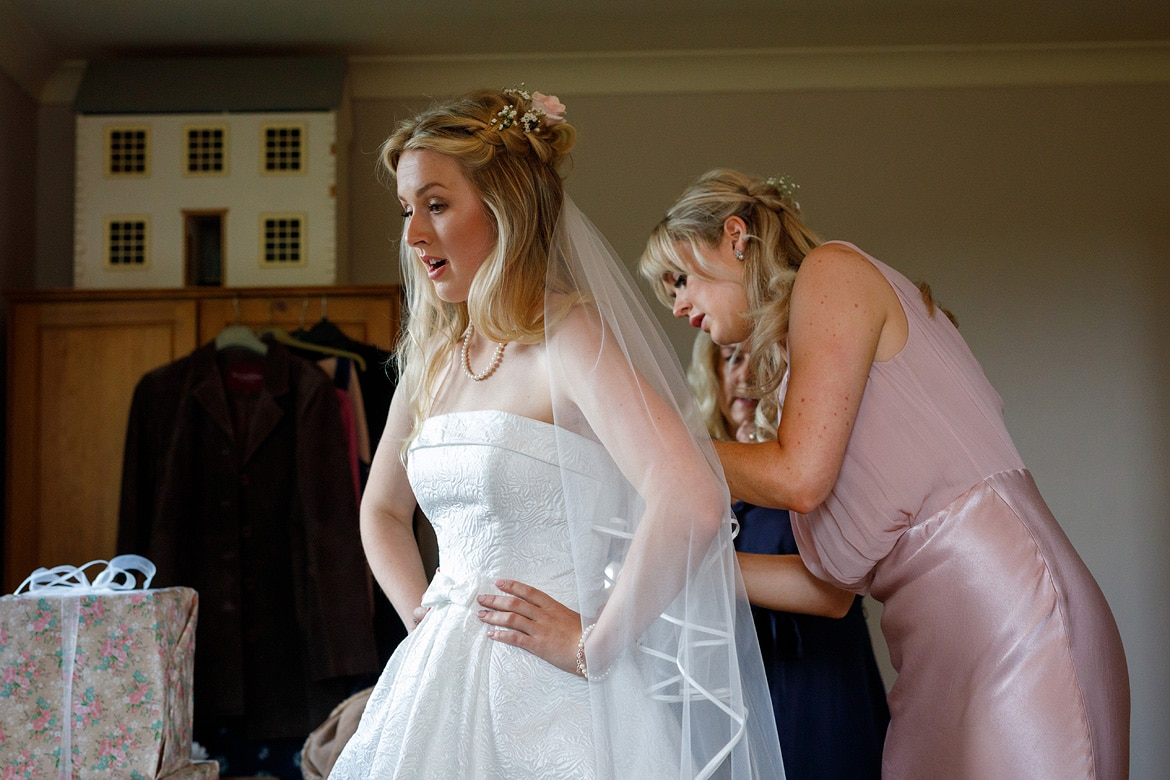 bridesmaids helping the bride dress