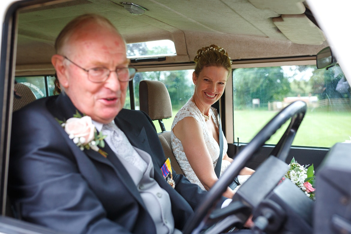 a bride arrives in the wedding landrover