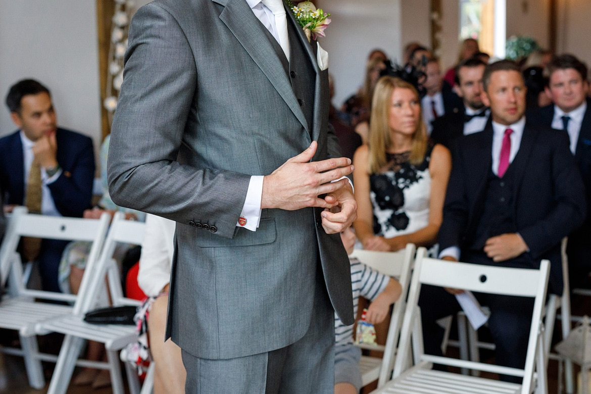 a groom waits nervously at a maidens barn wedding