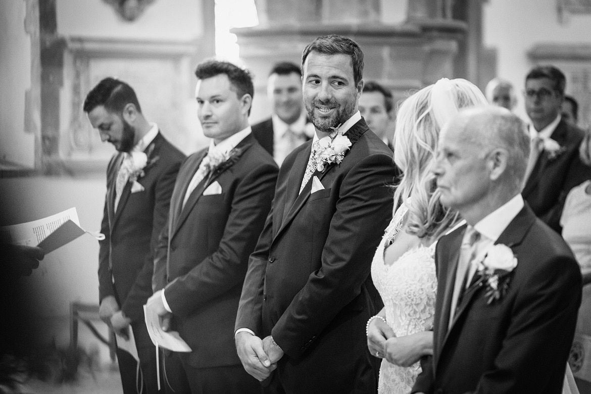 a groom glance at his bride as she arrives in church