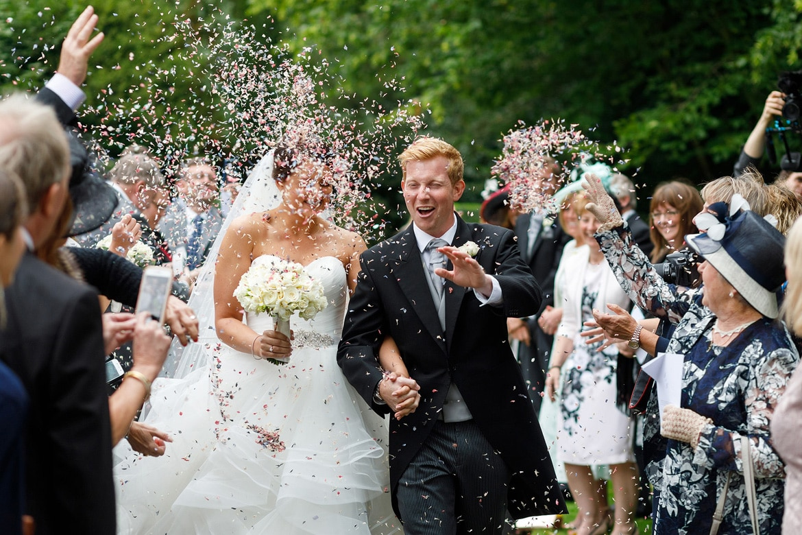 bride and groom walk through a storm of confetti at hengrave hall