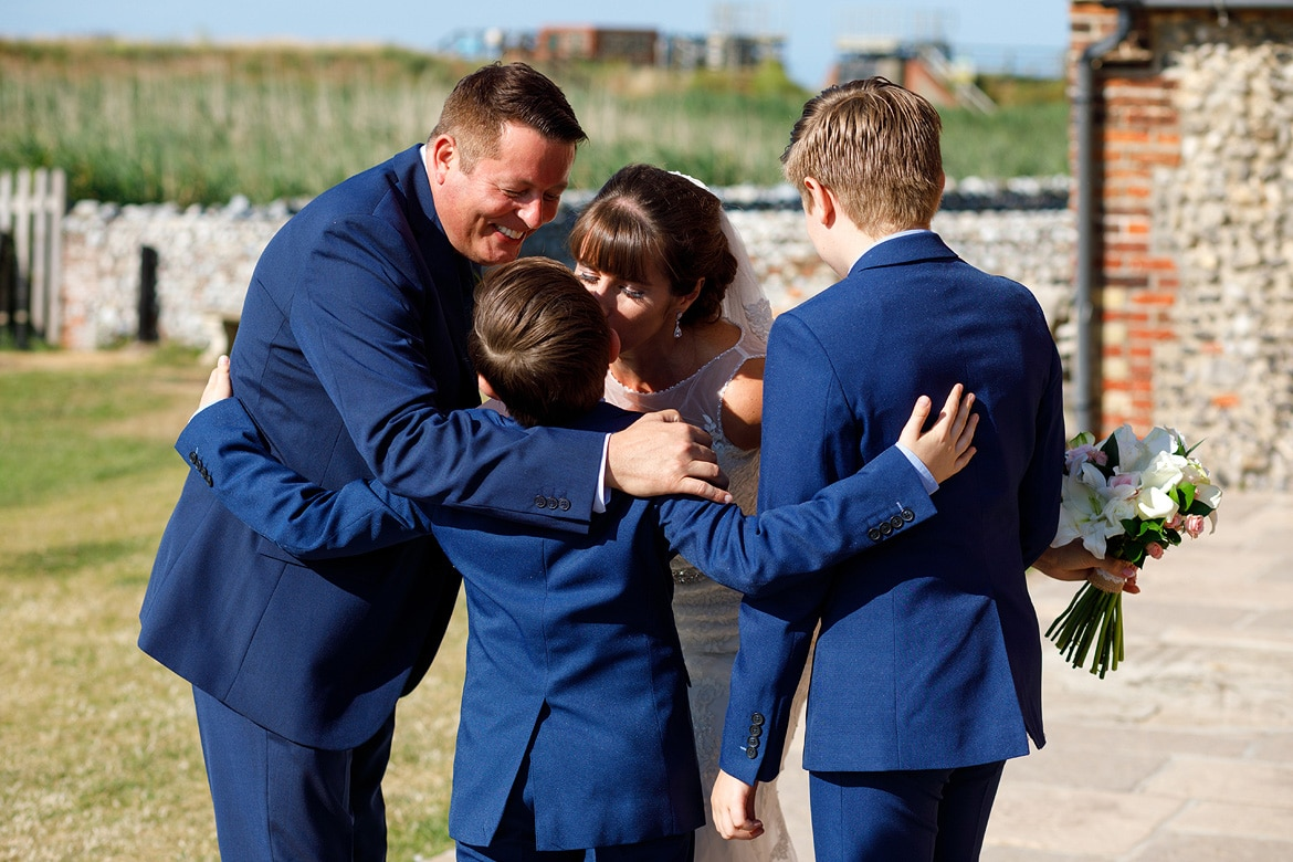 a family hug at a cley mill wedding