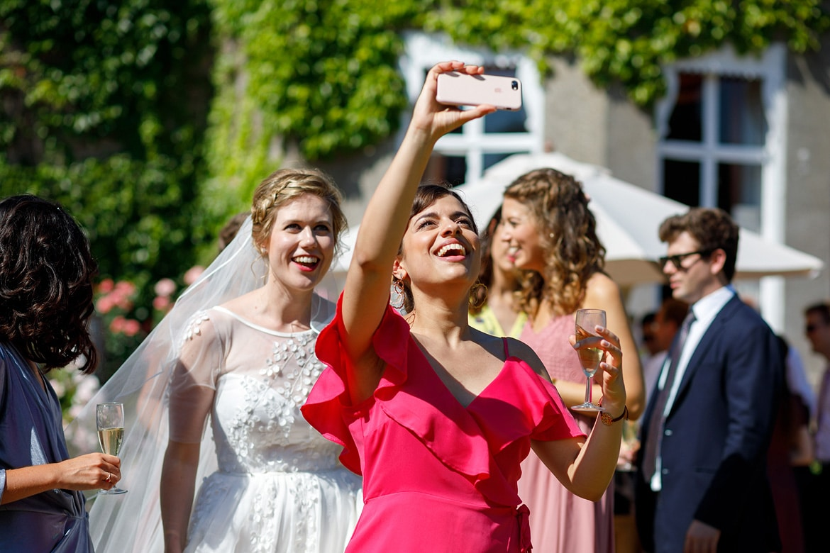 a guest takes a selfie with the bride