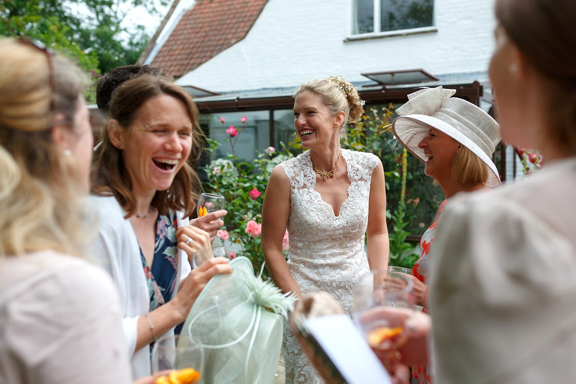the bride laughs with her friends at her norfolk wedding