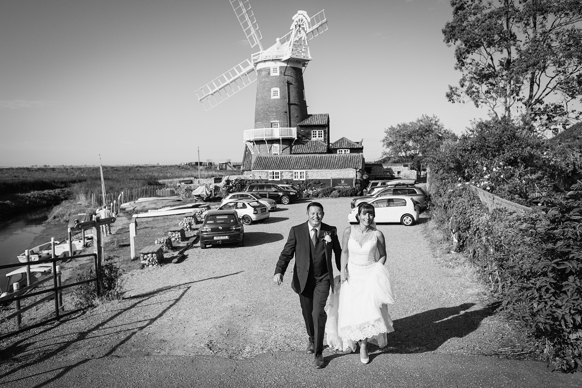 bride and groom walk away from cley windmill