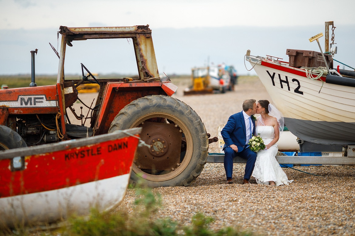 wedding portrait with the fishing boats on cley beach in north norfolk