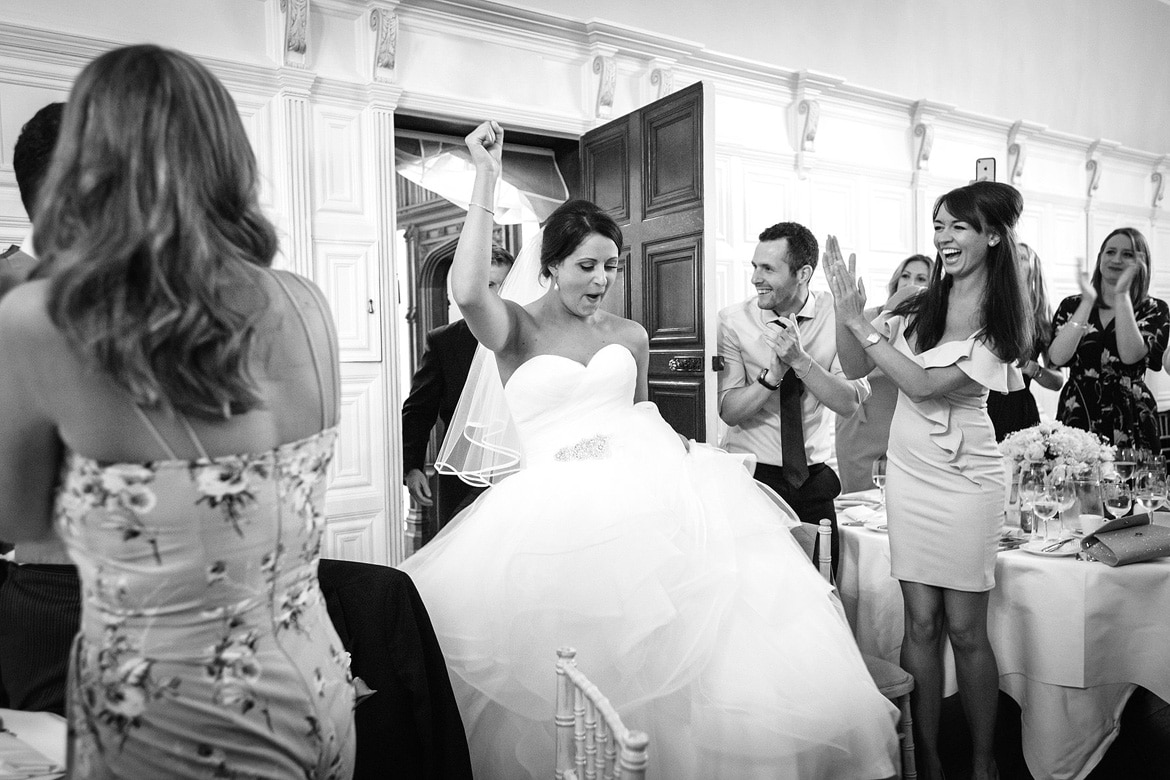 a bride making an entrance to the dining room at hengrave hall