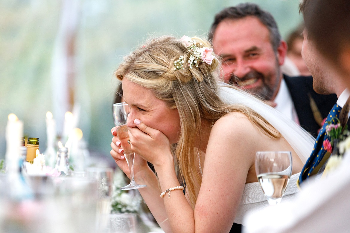 the bride laughs during the speeches of a suffolk wedding
