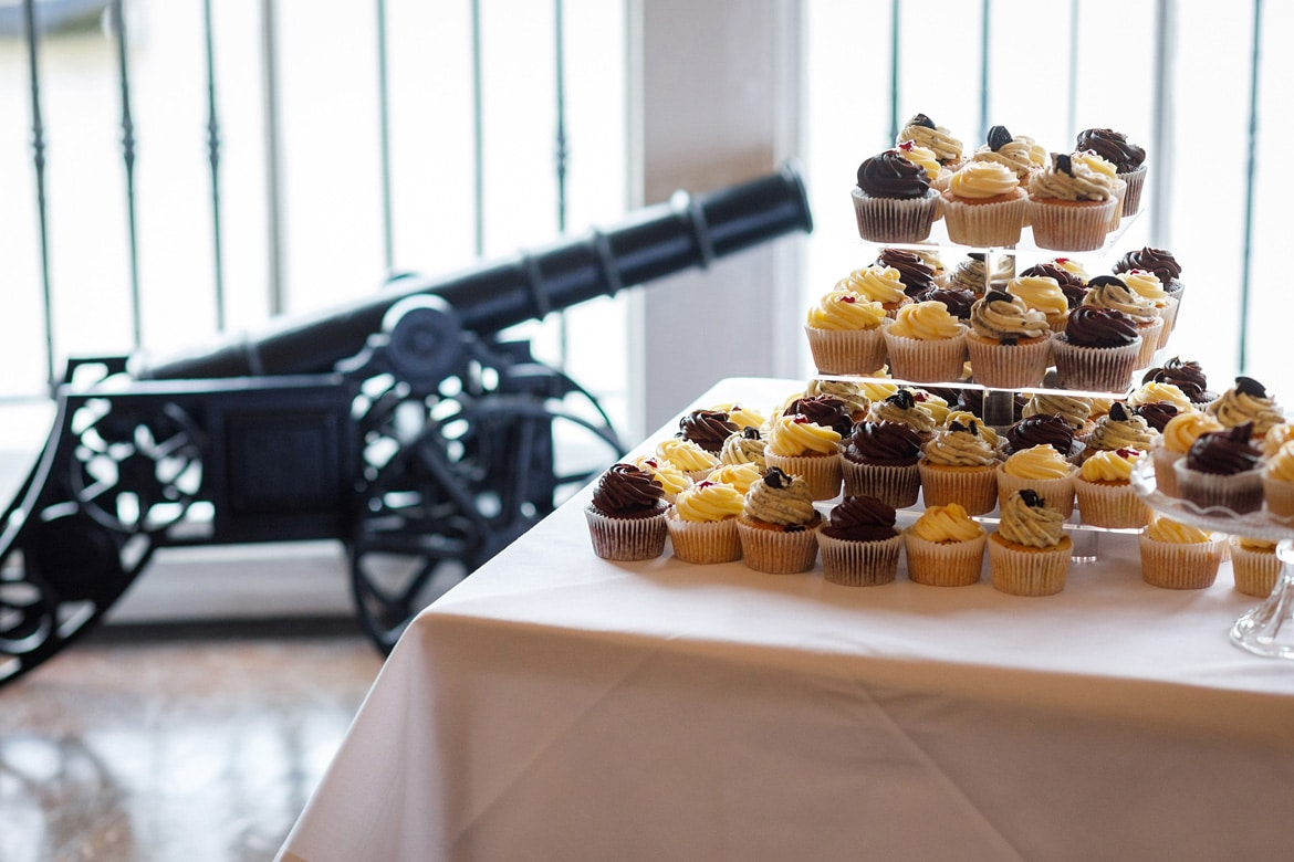the wedding cake with a cannon in the background