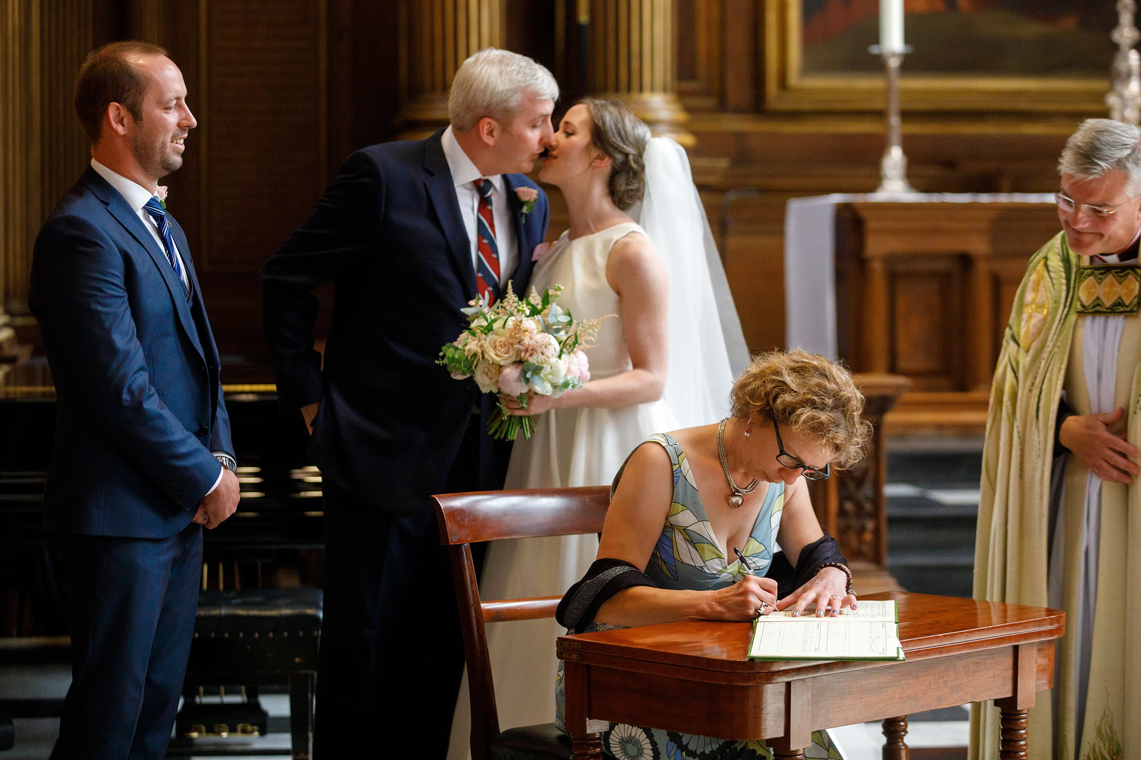 bride and groom kiss as a witness signs