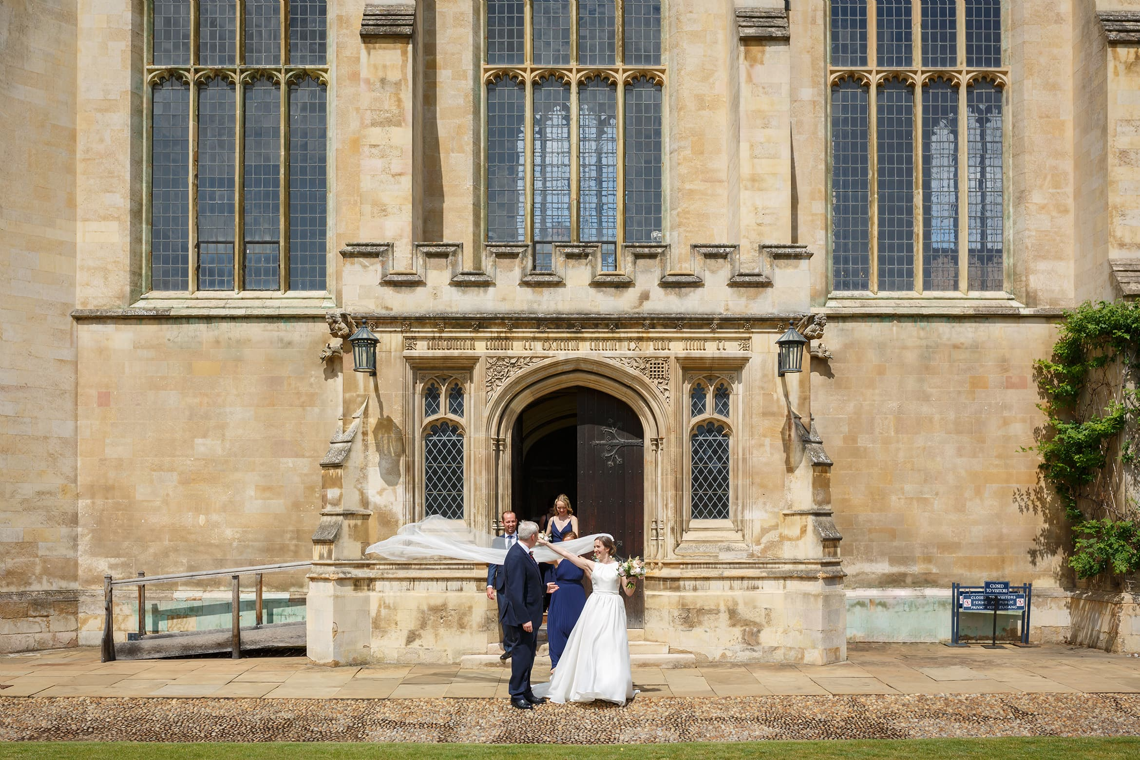 bride and groom outside trinity college cambridge