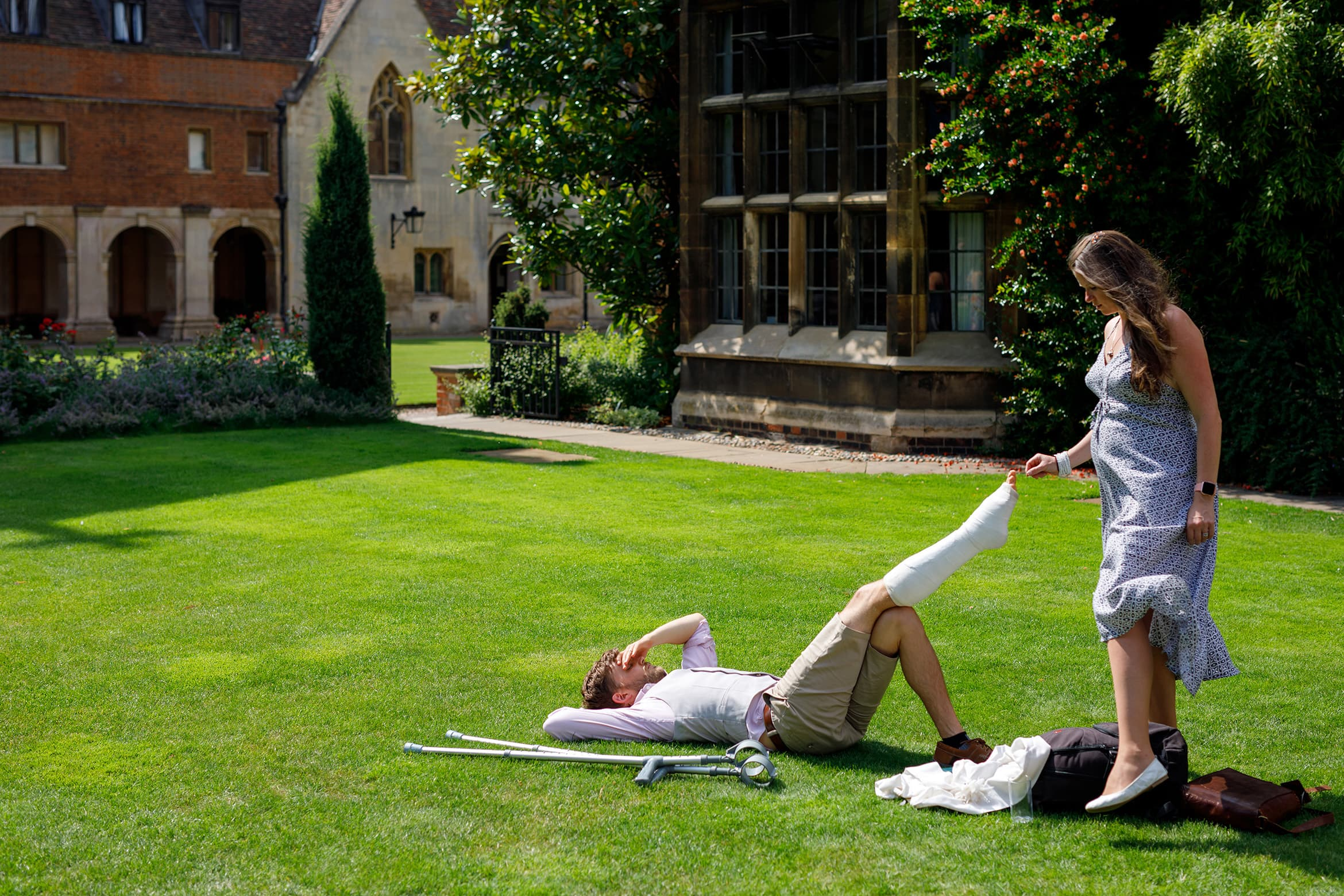 a wedding guest laying on the lawn at pembroke college wedding