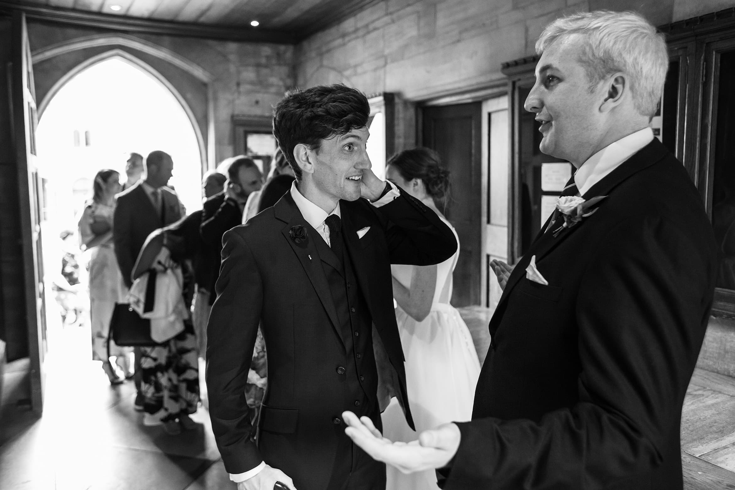 the groom greets a wedding guest