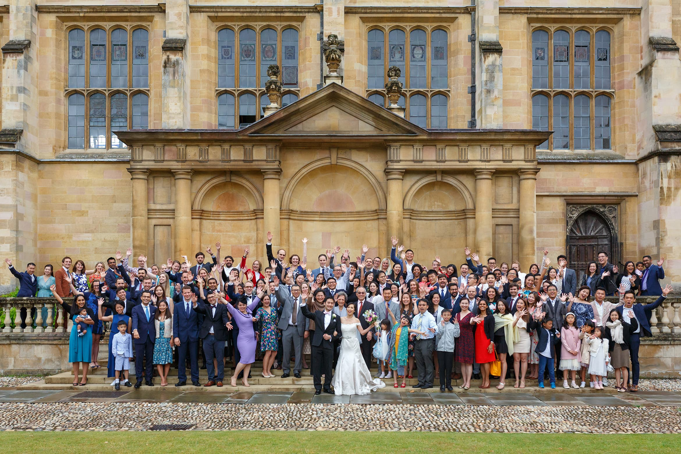 wedding guests on the tribune steps at trinity college cambridge