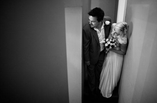 the couple peek into the room before a tuddenham mill wedding ceremony